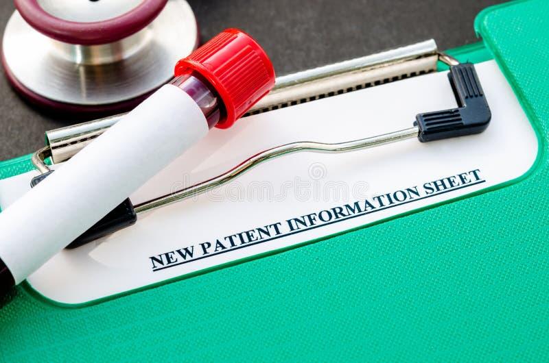 Prélevez le sang dans le tube pour l'essai et la nouvelle fiche d'informations patiente photographie stock libre de droits