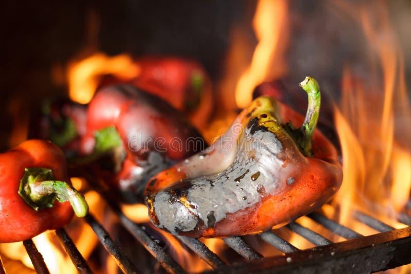 Préparant la délicatesse Ajvar du Balkan traditionnel, grillant le paprika sur une flamme nue image libre de droits