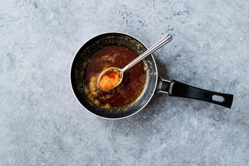Préparant la sauce rouge avec faire frire le beurre et les épices fondus la casserole/en faisant cuire la recette avec la cuillèr photographie stock