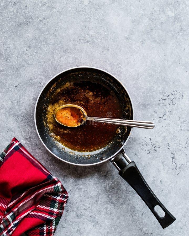 Préparant la sauce rouge avec faire frire le beurre et les épices fondus la casserole/en faisant cuire la recette avec la cuillèr image stock