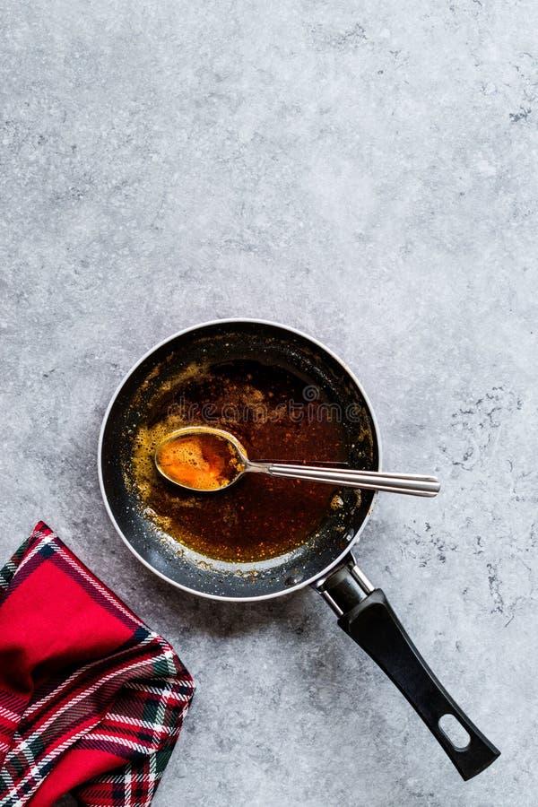Préparant la sauce rouge avec faire frire le beurre et les épices fondus la casserole/en faisant cuire la recette avec la cuillèr images libres de droits
