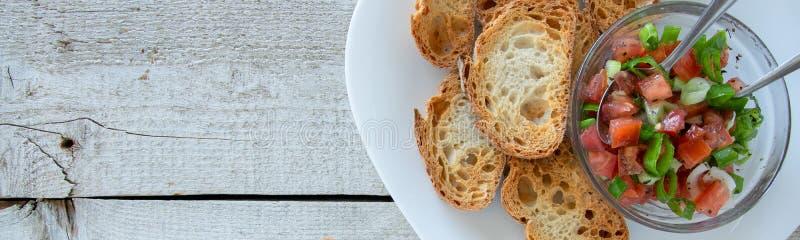 Préparant les apéritifs italiens de tomate savoureuse - bruschette, sur des tranches de baguette grillée image stock