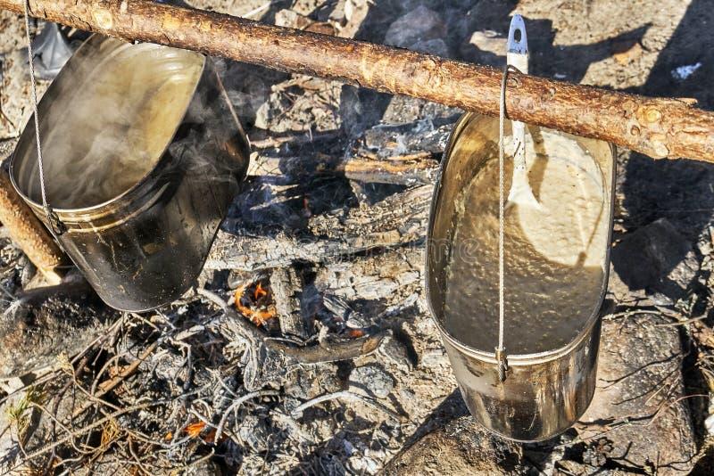 Préparation d'un petit déjeuner sur le feu dans une hausse image stock