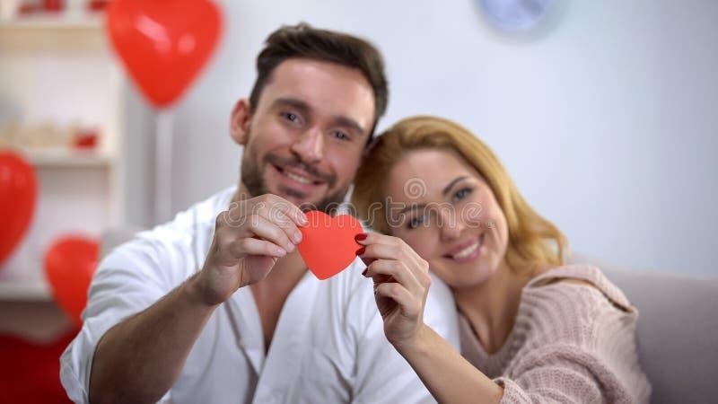 Préparation de jour de valentines, couple souriant et montrant au coeur de papier rouge de caméra image libre de droits