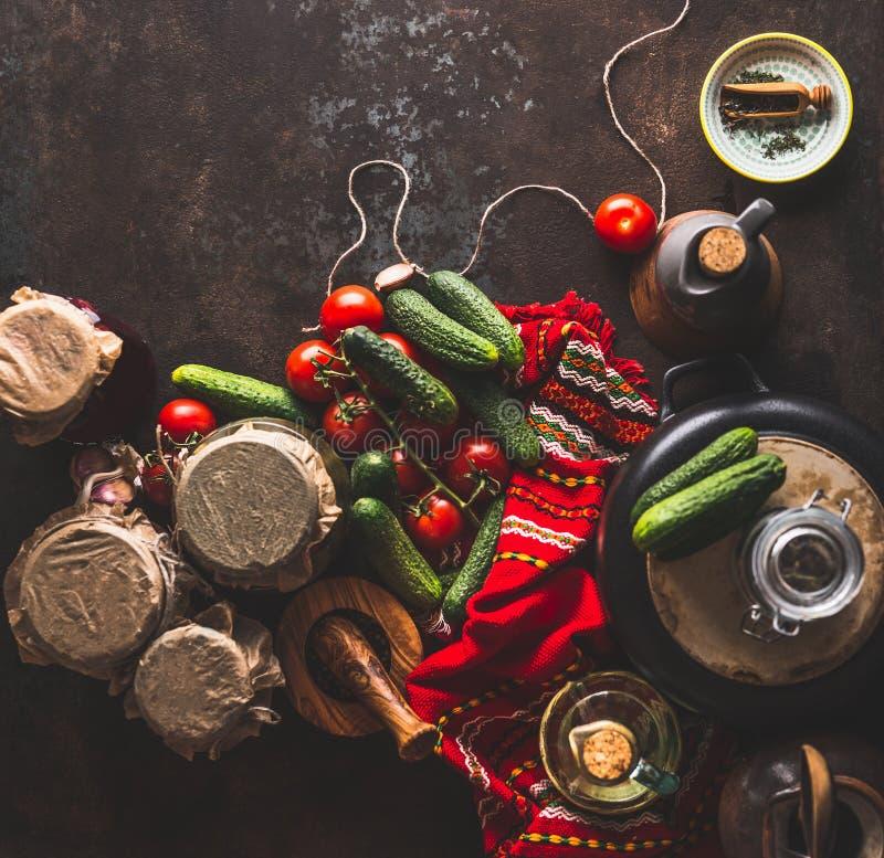 Préparation de légumes de conserves au vinaigre sur le fond rustique foncé avec les ingrédients, la bouteille au vinaigre, l'assa image libre de droits