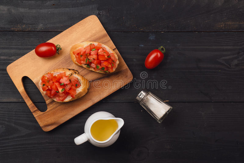 Préparation de la bruschette italienne délicieuse de tomate avec le veget coupé photographie stock