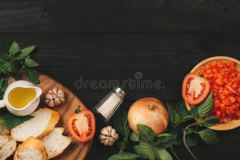 Préparation de la bruschette italienne délicieuse de tomate avec les légumes, les herbes et le pétrole coupés photographie stock libre de droits