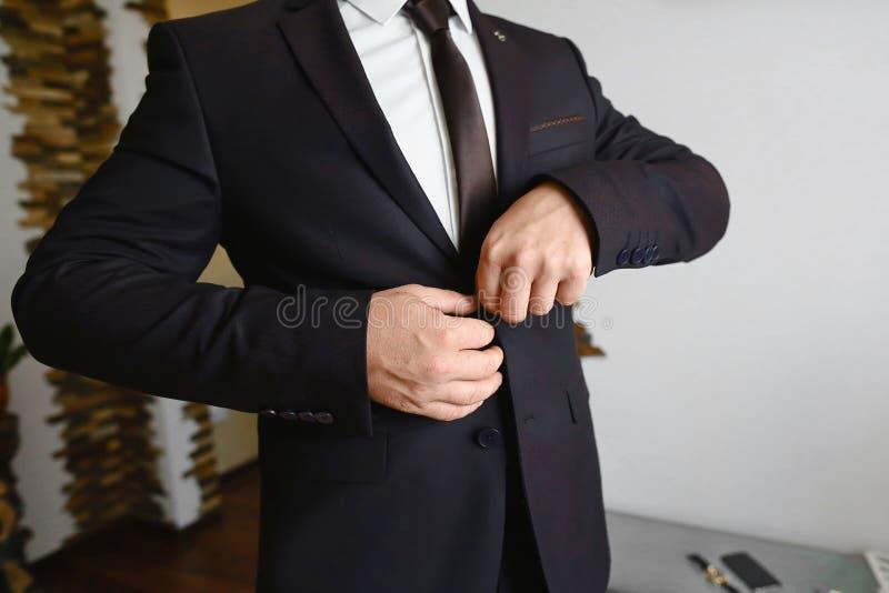 Préparation de matin de mariés, marié beau obtenant habillé et se préparant au mariage, dans le costume brun foncé photographie stock libre de droits