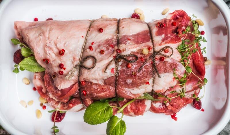Préparation de rôti de viande crue avec les herbes, les épices, les pignons et les canneberges à cuire frais, vue supérieure image libre de droits