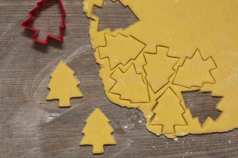 Préparation des biscuits de gingembre La coupe a figuré des biscuits sous la forme d'arbre de Noël images stock
