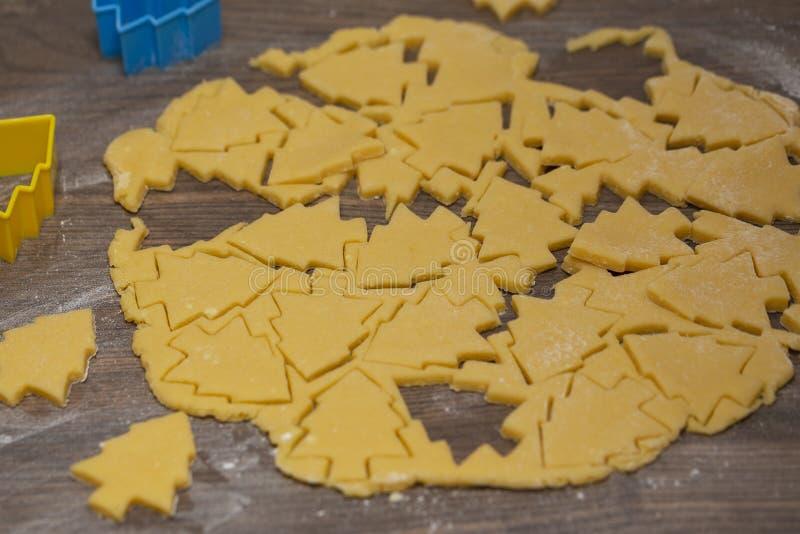 Préparation des biscuits de gingembre La coupe a figuré des biscuits sous la forme d'arbre de Noël image libre de droits