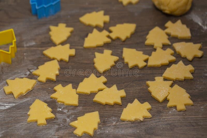Préparation des biscuits de gingembre La coupe a figuré des biscuits sous la forme d'arbre de Noël photographie stock