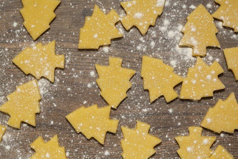 Préparation des biscuits de gingembre La coupe a figuré des biscuits sous la forme d'arbre de Noël photo stock