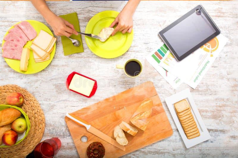 Préparation du petit déjeuner tout en obtenant la documentation en ligne au sujet du nutri images stock