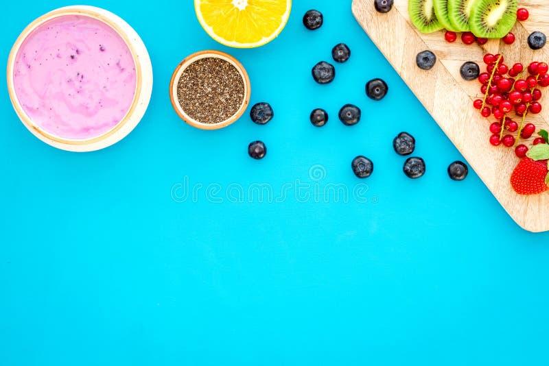Préparation du smoothie sain de fruit Bol de smoothie d'Acai près de planche à découper avec des fruits frais, baies, graines de  image stock