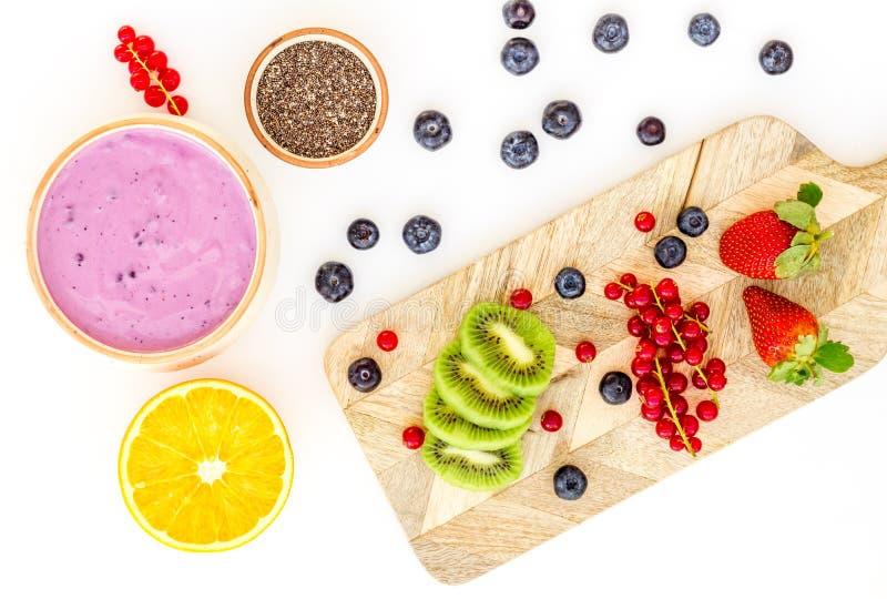 Préparation du smoothie sain de fruit Bol de smoothie d'Acai près de planche à découper avec des fruits frais, baies, graines de  photos libres de droits
