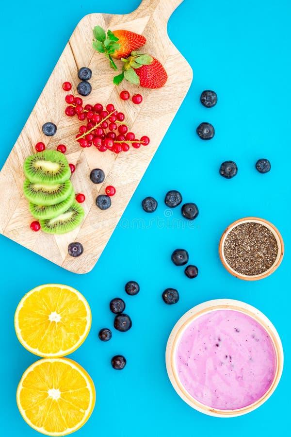Préparation du smoothie sain de fruit Bol de smoothie d'Acai près de planche à découper avec des fruits frais, baies, graines de  images libres de droits