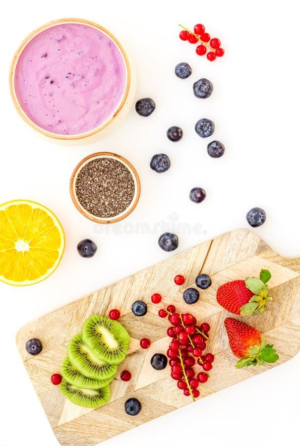 Préparation du smoothie sain de fruit Bol de smoothie d'Acai près de planche à découper avec des fruits frais, baies, graines de  image libre de droits