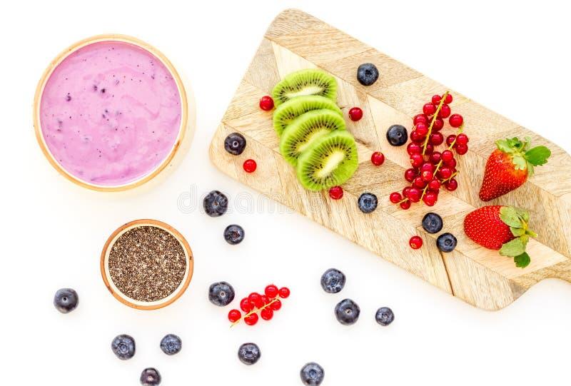 Préparation du smoothie sain de fruit Bol de smoothie d'Acai près de planche à découper avec des fruits frais, baies, graines de  photo stock