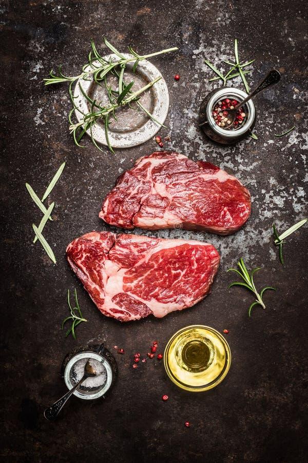 Préparation fraîche de bifteck de Ribeye de viande crue avec des herbes, des épices et le pétrole sur le fond rustique foncé en m photographie stock libre de droits