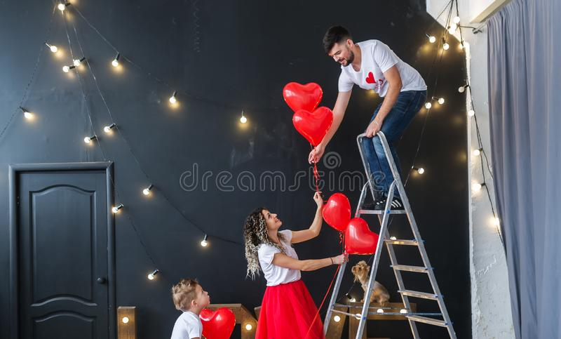 Préparation pour le jour du ` s de St Valentine La jeune famille accroche les ballons rouges de fête de coeur photos stock