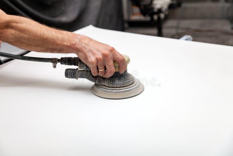Préparation pour peindre un élément de voiture utilisant la ponceuse et le mastic par un technicien de service nivelant avant d'a photo stock