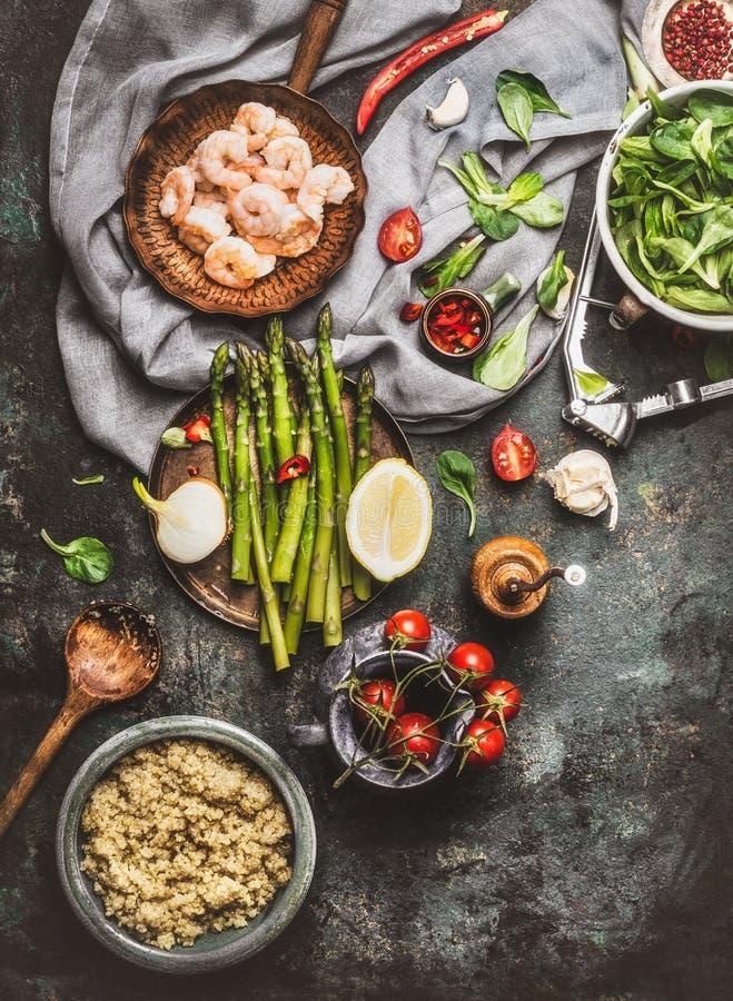 Préparation savoureuse de salade de quinoa avec la cuillère en bois, les crevettes, l'asperge et les divers légumes sains sur le  images libres de droits