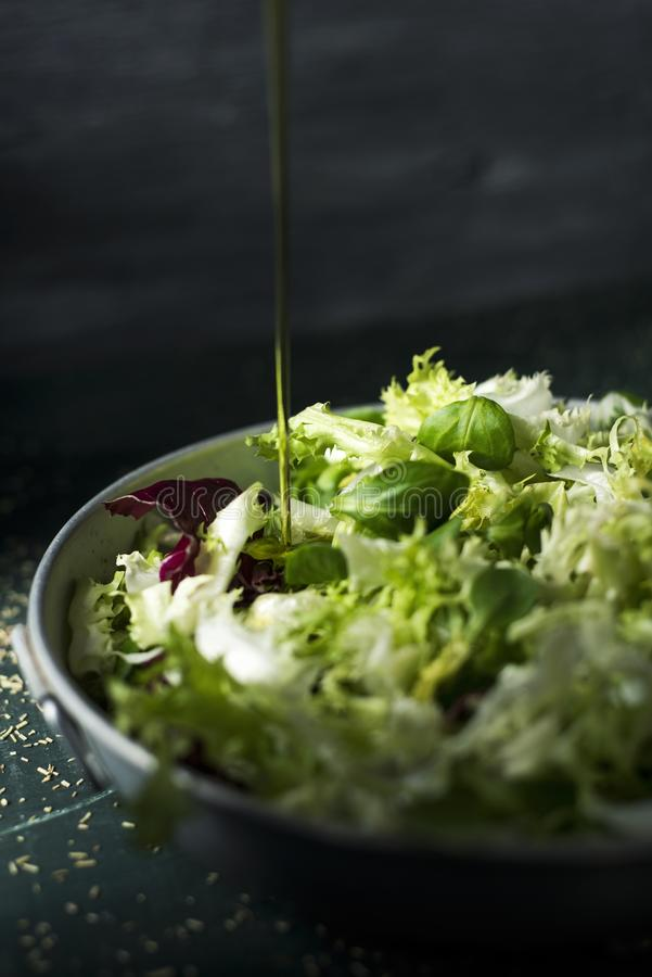 Préparer une salade verte avec l'huile d'olive photos stock