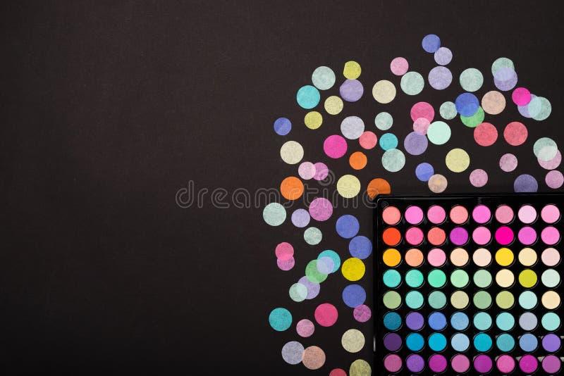 Préparez la palette de fard à paupières avec des confettis dispersés sur le fond noir image libre de droits