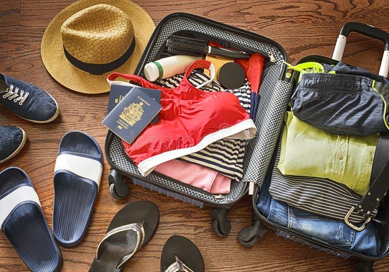 Préparez les accessoires et les articles de voyage Ouvrez le sac du ` s de voyageur avec l'habillement, les accessoires, et le pa photographie stock