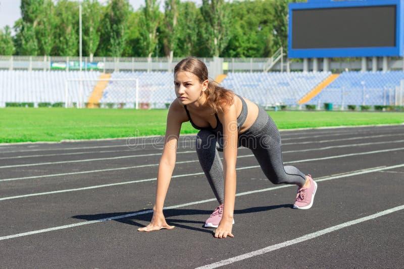 Préparez pour aller Photo haute étroite d'athlète féminin sur la ligne de départ de bas début Fille sur la voie de stade, se prép images libres de droits