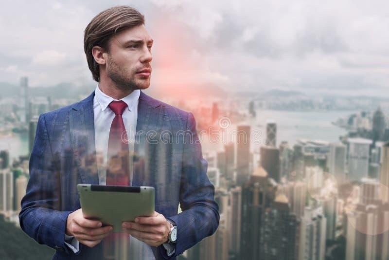 Préparez pour fonctionner Homme d'affaires barbu élégant tenant son comprimé numérique tout en se tenant sur du fond de paysage u images stock