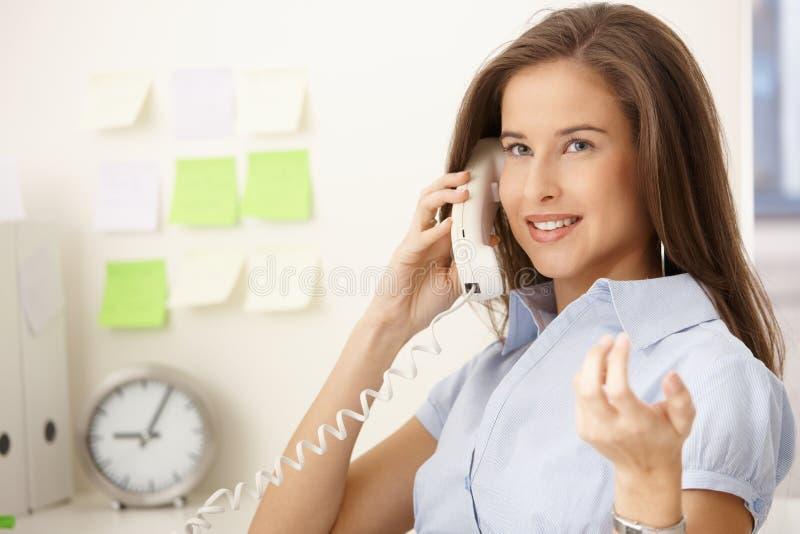 Préposée de bureau heureuse à l'appel images stock