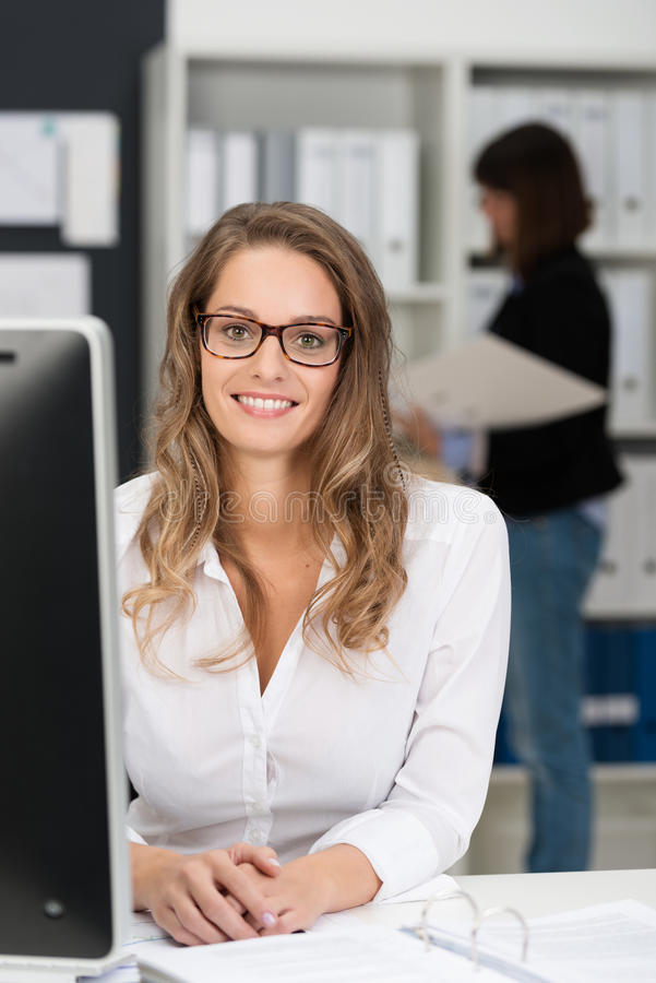 Préposée de bureau s'asseyante dans blanc regardant l'appareil-photo image stock