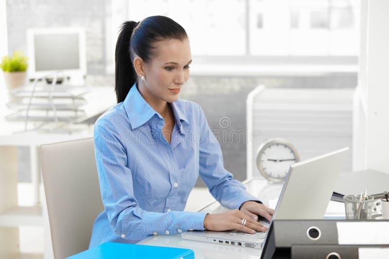 Préposée de bureau travaillant sur l'ordinateur portable images stock