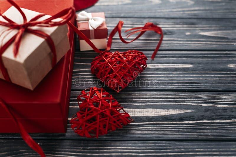 Présent élégant de rouge et deux rubans de coeur sur en bois rustique noir image stock