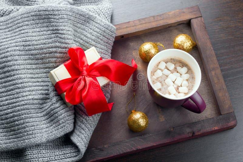 Présent avec l'arc rouge, boisson chaude avec la guimauve et boules d'or de Noël photographie stock libre de droits