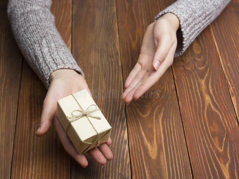 Présent, cadeau Fermez-vous des mains femelles tenant le petit cadeau photo libre de droits