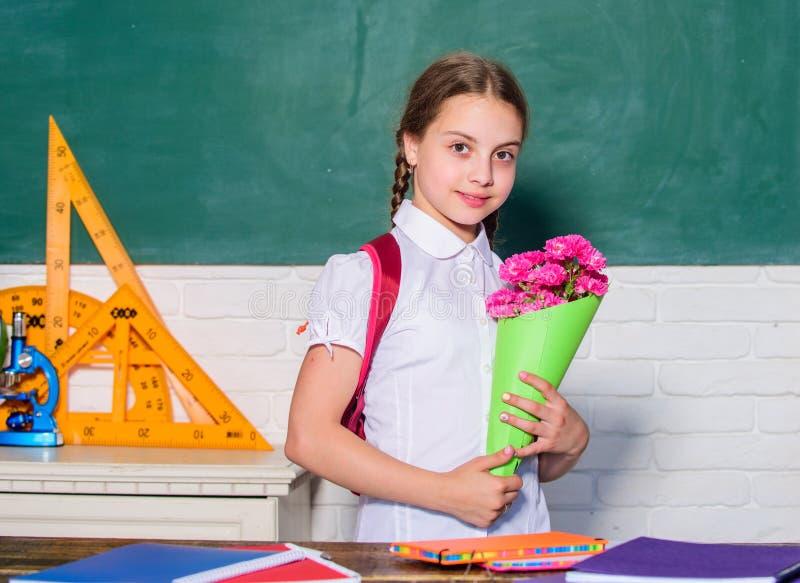 Présent de fleur pour le meilleur professeur le jour de la connaissance est le 1er septembre petit enfant de fille d'école avec l photo stock