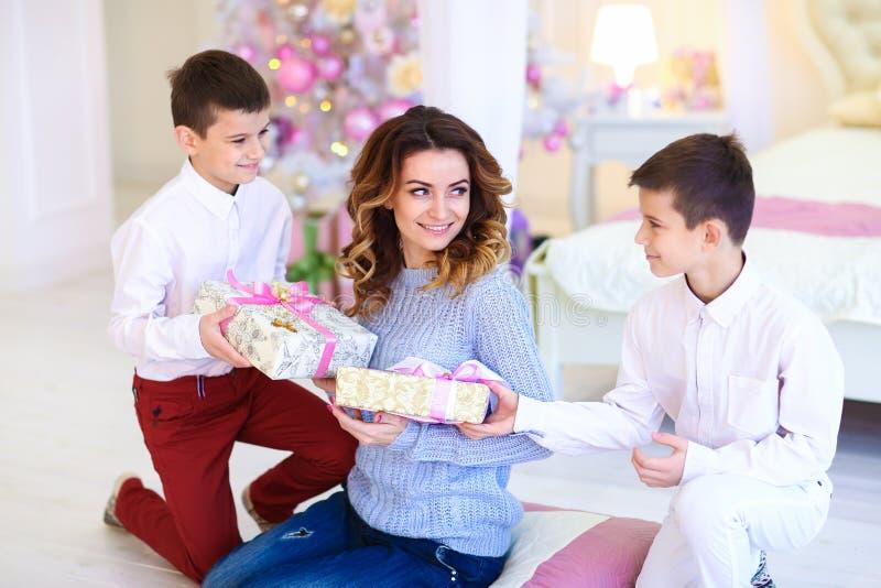 Présent doué de deux fils heureux pour la mère près de l'arbre de sapin décoré photo libre de droits