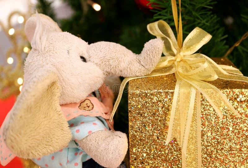 Présent pour vous ! une poupée mignonne d'éléphant tenant le boîte-cadeau de scintillement d'or avec l'arc de ruban d'or photos stock