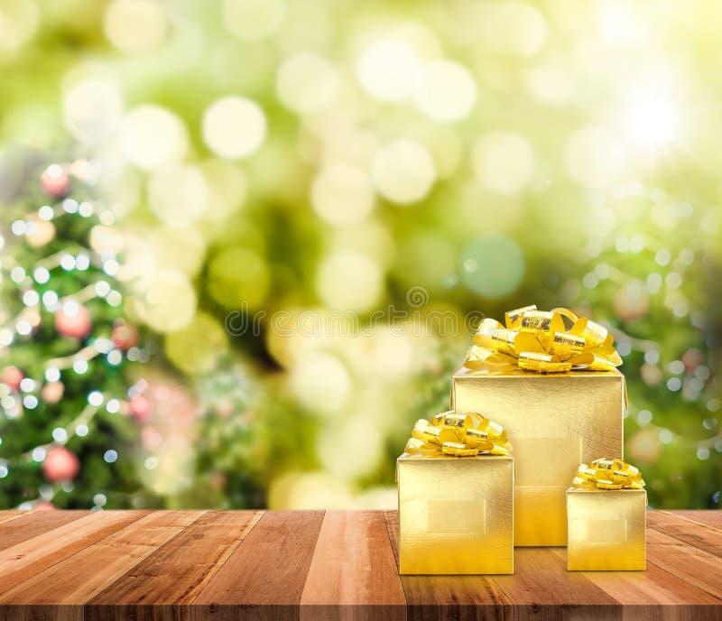 Présents d'or sur le dessus de table en bois de planche avec la tache floue d'arbre de Noël images stock