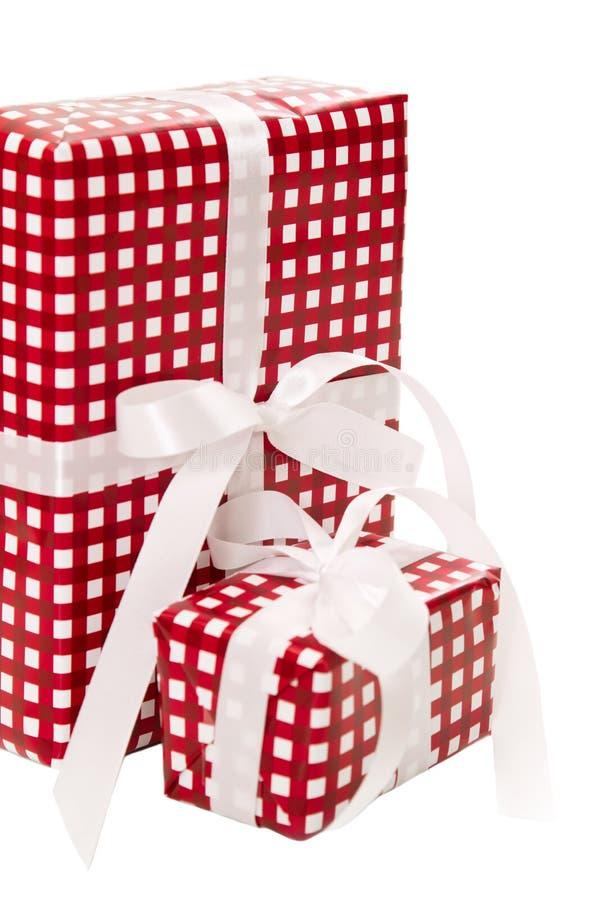 Présents enveloppés en papier rouge à carreaux avec un ruban blanc image libre de droits