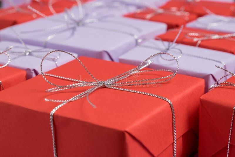 Présents enveloppés en papier rouge et lilas en tant que fond de fête images stock
