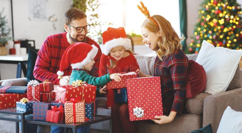 Présents ouverts de famille heureuse le matin de Noël photos stock