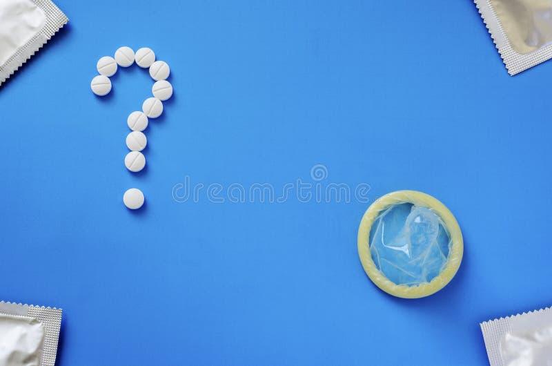 Préservatif et point d'interrogation des comprimés sur un fond bleu photos stock