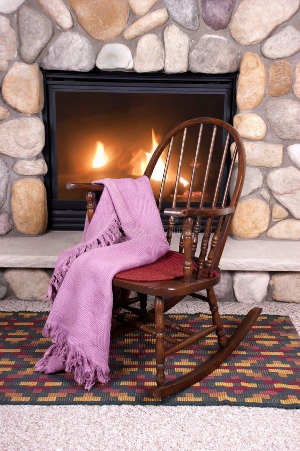 Présidence d'oscillation en bois devant la cheminée à la maison photographie stock libre de droits