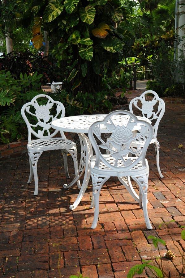 Présidences de jardin blanches dans un patio d'arrière-cour photos libres de droits