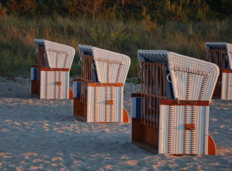 Présidences de plage en lumière de soirée images stock