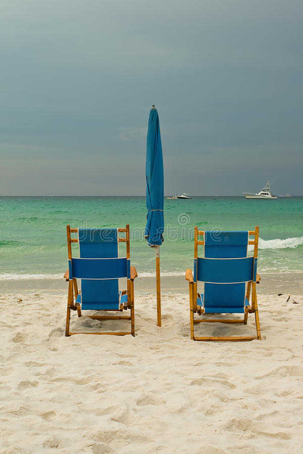 Présidences de salon de plage au-dessus de ciel nuageux image stock
